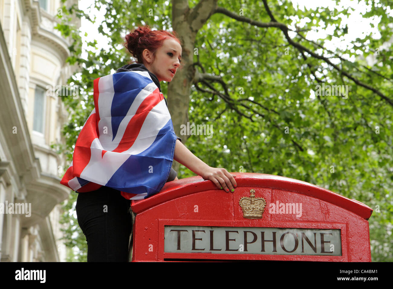A girl climbs onto a telephone box to watch the Queen's Diamond Jubilee carriage procession, London - Stock Image
