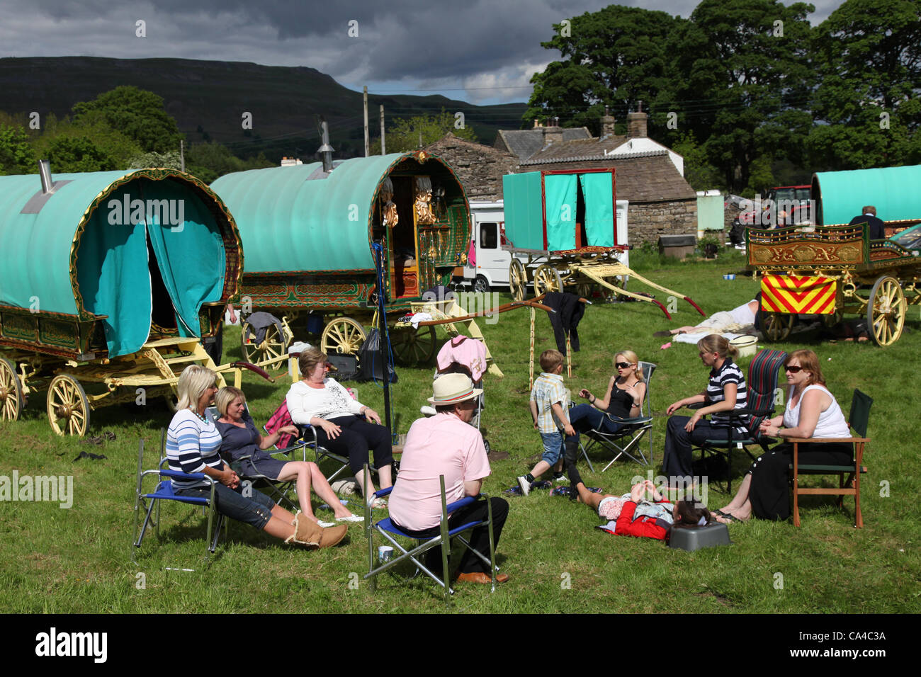 "Family camp fire with Vardo Caravan Traditional horse-drawn Gypsy caravans or ""Bow Top"" canvas covered Wagons en - Stock Image"