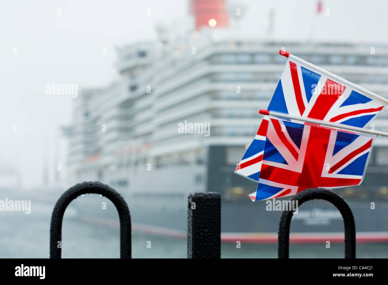 SOUTHAMPTON, UK, 5th June 2012. Spectators with union jack flags view the Queen Elizabeth cruise liner during the - Stock Image