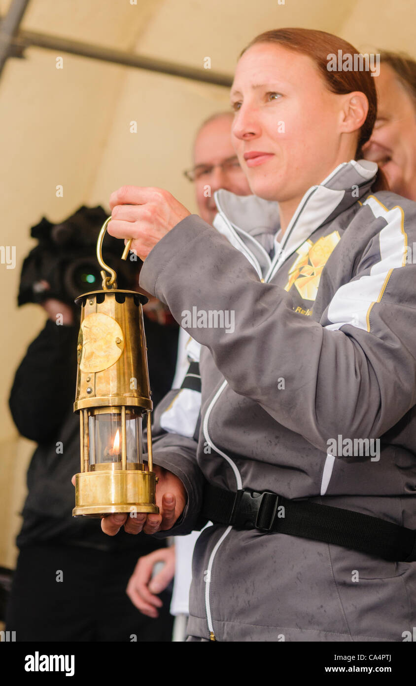 The Olympic Flame in its Davy Lamp lantern is held up - Stock Image