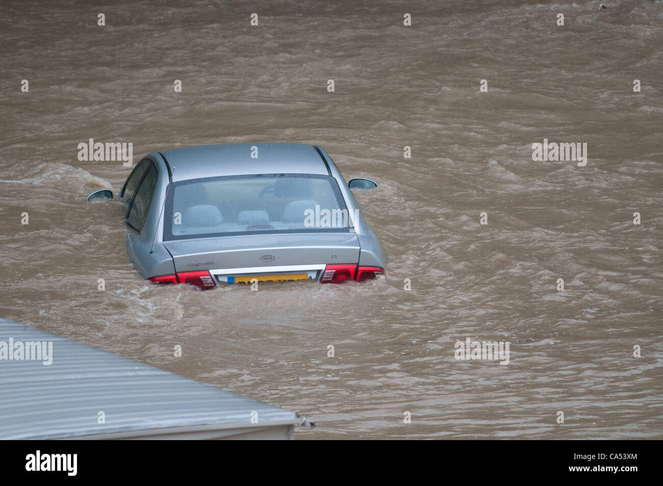 Ceredigion, Wales, UK. Saturday June 9 2012. A car is submerged by the waters of the River Leri at the Riverside - Stock Image