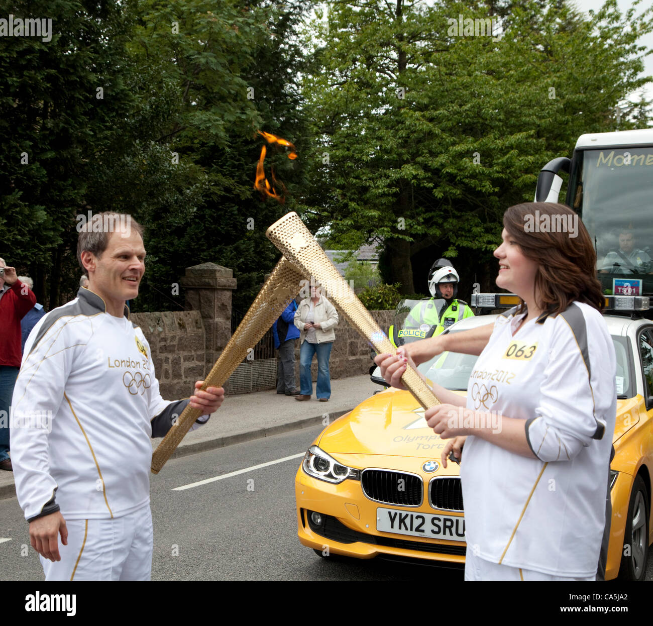 Aboyne, Scotland - June 11, 2012: Karl Kaufmann passing the Olympic flame to Amanda Yule during the 2012 Olympic - Stock Image