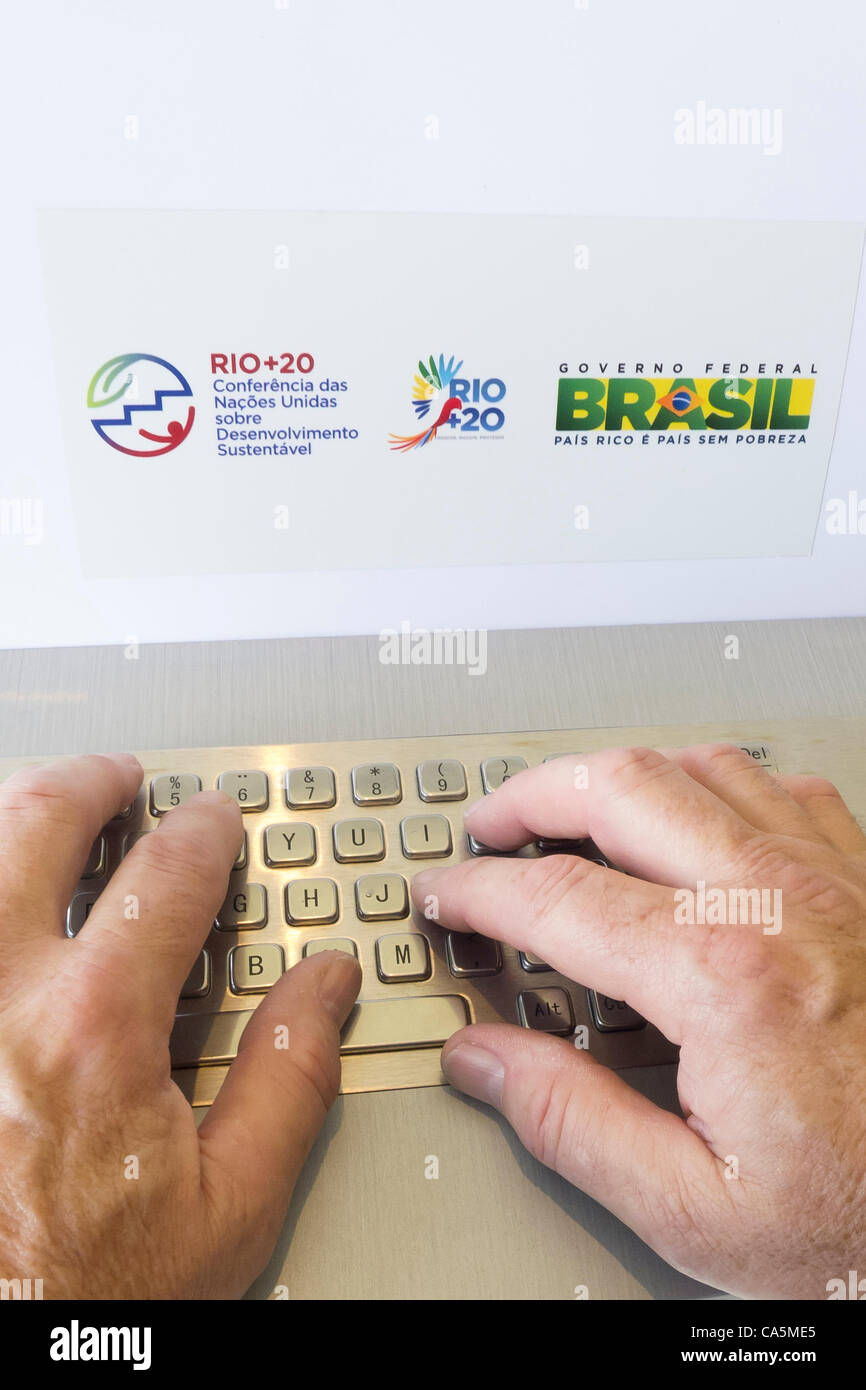 A man is typing on the keyboard of a dedicated information computer with a Rio+20 sticker and a Brazil governmnet - Stock Image