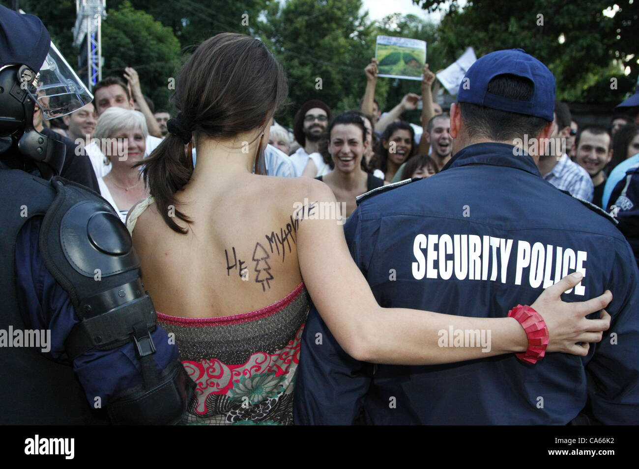 Woman demonstrator with a protest slogan written on her shoulder putting his arm around a policeman's shoulder. - Stock Image