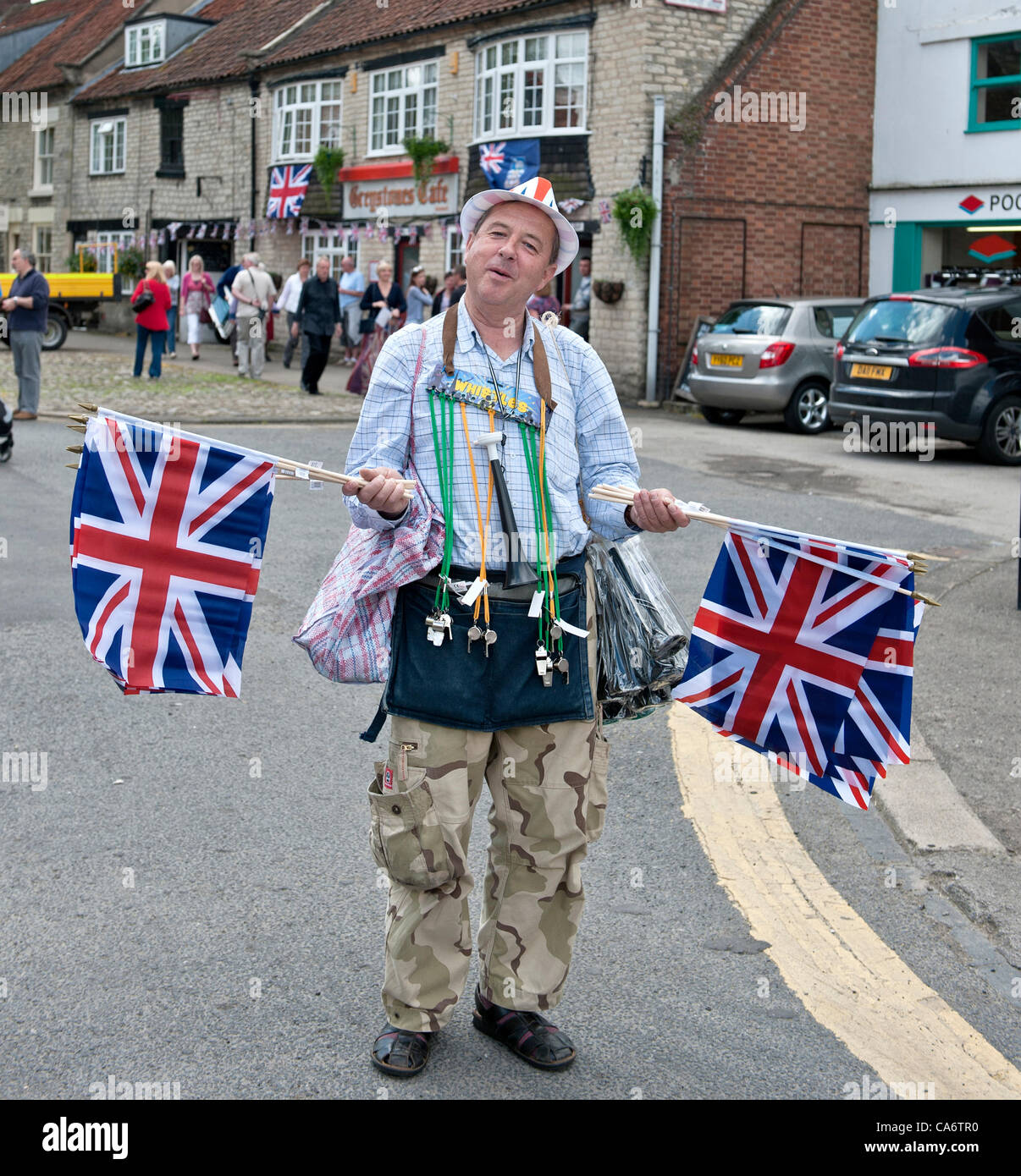 A flag seller in Pickering plies his wares at Pickering during the Olympic torch relay - Stock Image