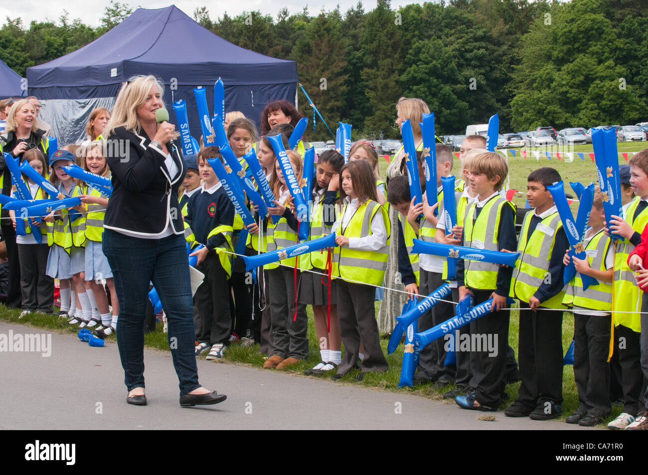 Radio Leeds presenter Georgey Spanswick entertaining & talking to the crowd (schoolchildren) standing & - Stock Image