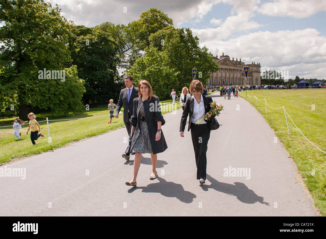 Smiling, happy Princess Beatrice (left) walks up the main drive of Harewood House after celebrating the arrival - Stock Image