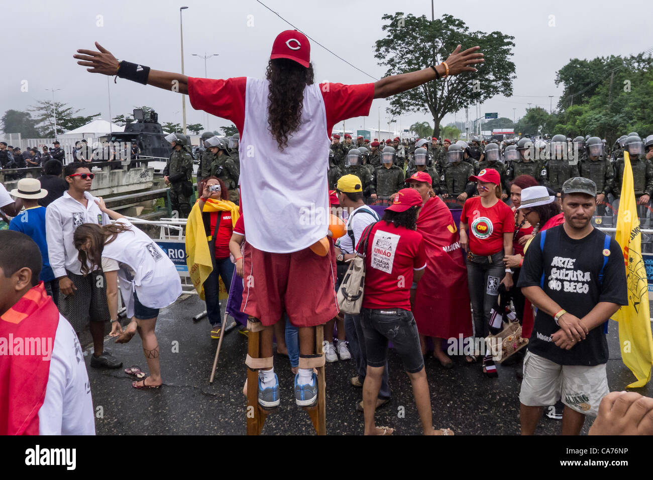 A demonstrator on stilts faces shock troops across a barrier at a demonstration by indigenous people, the Landless - Stock Image