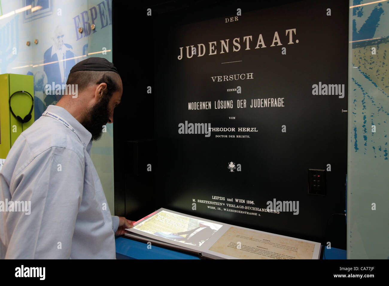 A religious Jewish man inspecting an interactive wall about Zionism during the opening ceremony of the Presidium - Stock Image