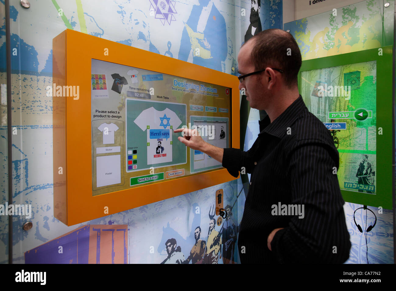 A visitor designing a shirt with Jewish symbols at an interactive wall installation about Zionism during the opening - Stock Image