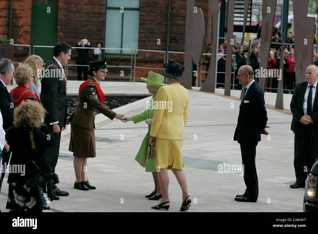 Her Majesty the Queen accompanied by Dame Mary Peters, is greeted by a Cadet at the Belfast Titanic building which - Stock Image