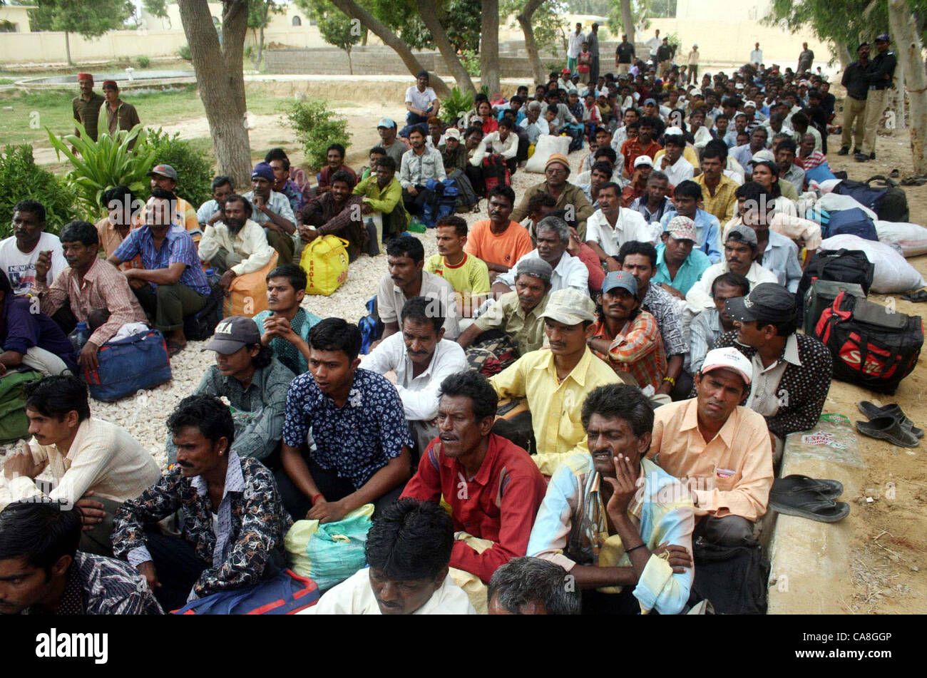 Freed Indian fishermen, who were imprisoned for violating  territorial waters, sit in queues before their release - Stock Image