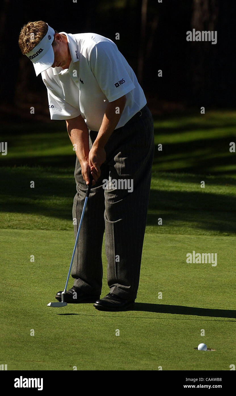 Luke Donald watches as the ball falls into the cup on the 18th green of Poppy Hills for a birdie during the AT&T - Stock Image