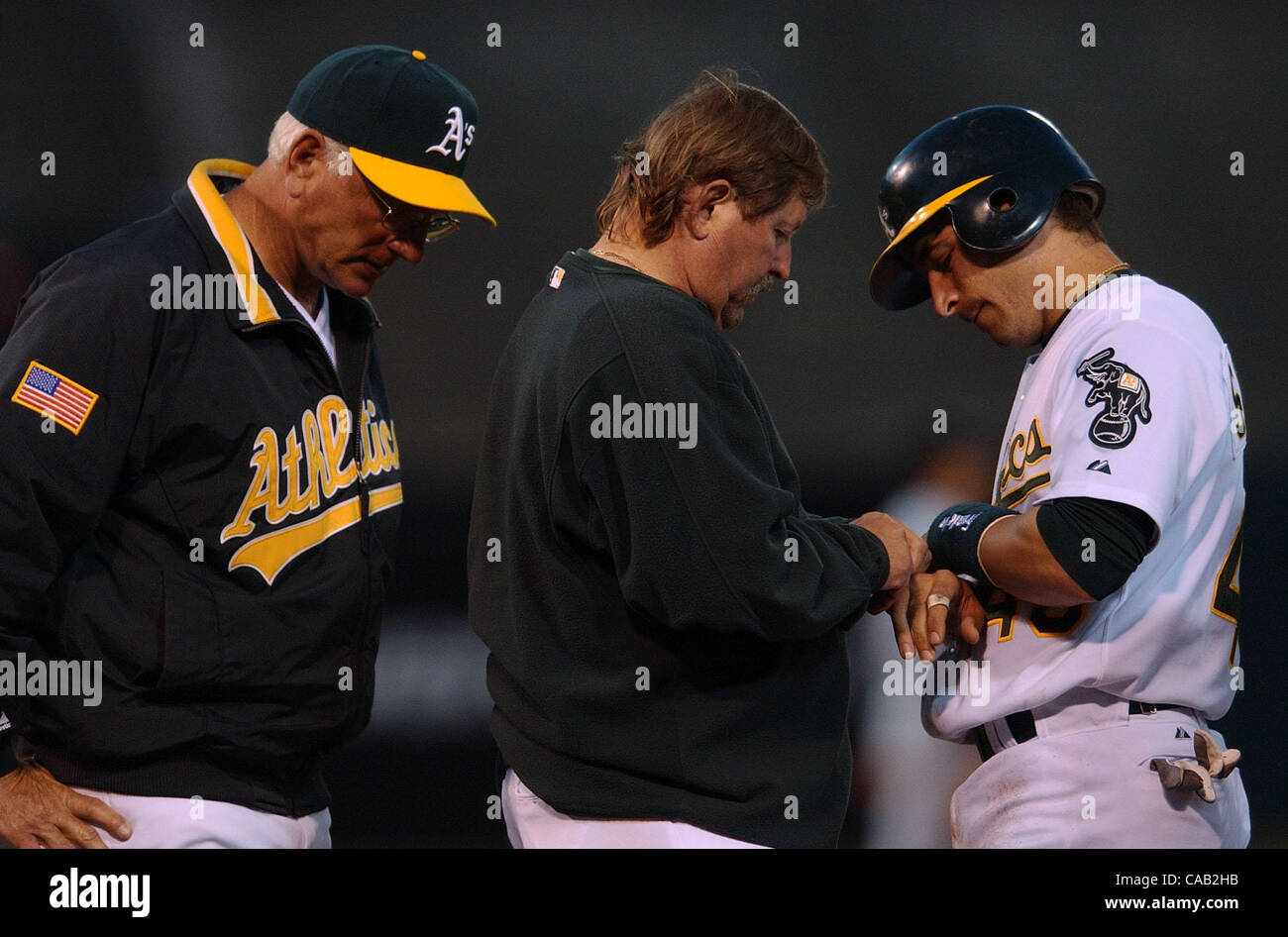 Oakland Athletics Marco Scutaro, #49, is examined by trainer Larry ...