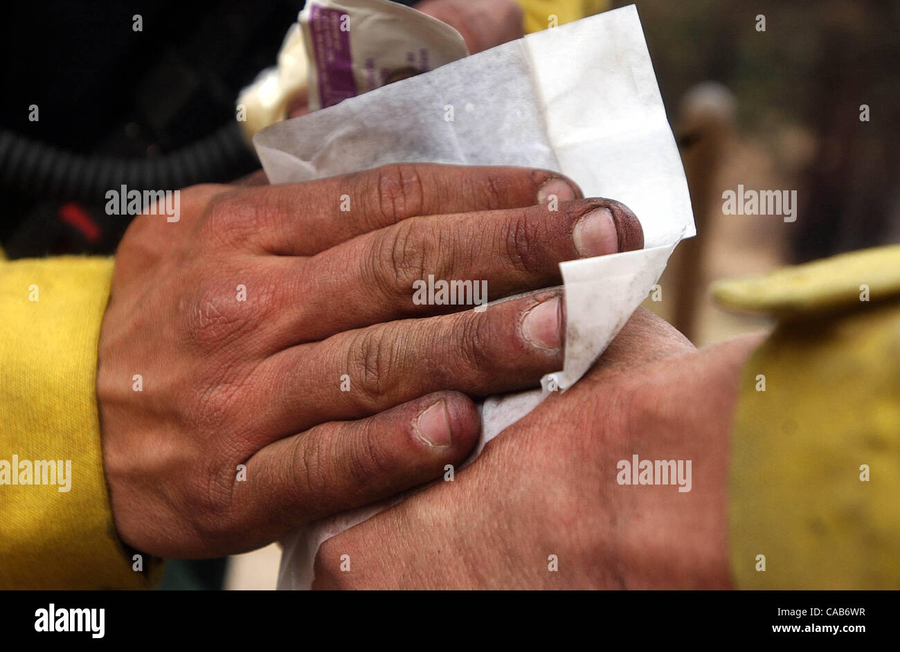 Jul 16, 2004; Carson City, CA, USA; Squad boss JAMES RYAN tends to blistered hand of fellow Bureau of Indian Affairs Stock Photo