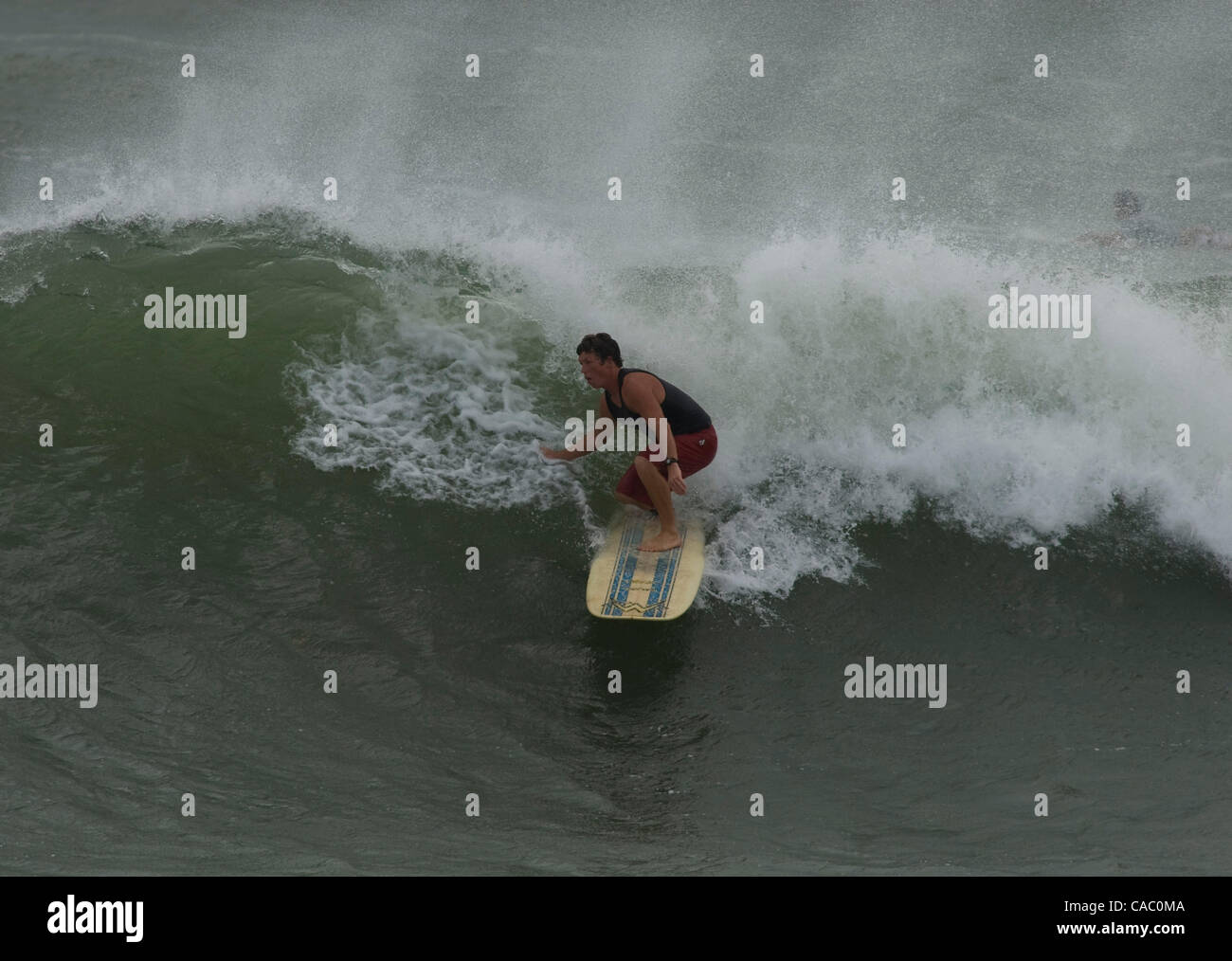 June 29, 2010 - Port Aransas, Texas, USA - 06/29/2010. A surfer catches a wave in Aransas Pass, Texas as swell from - Stock Image
