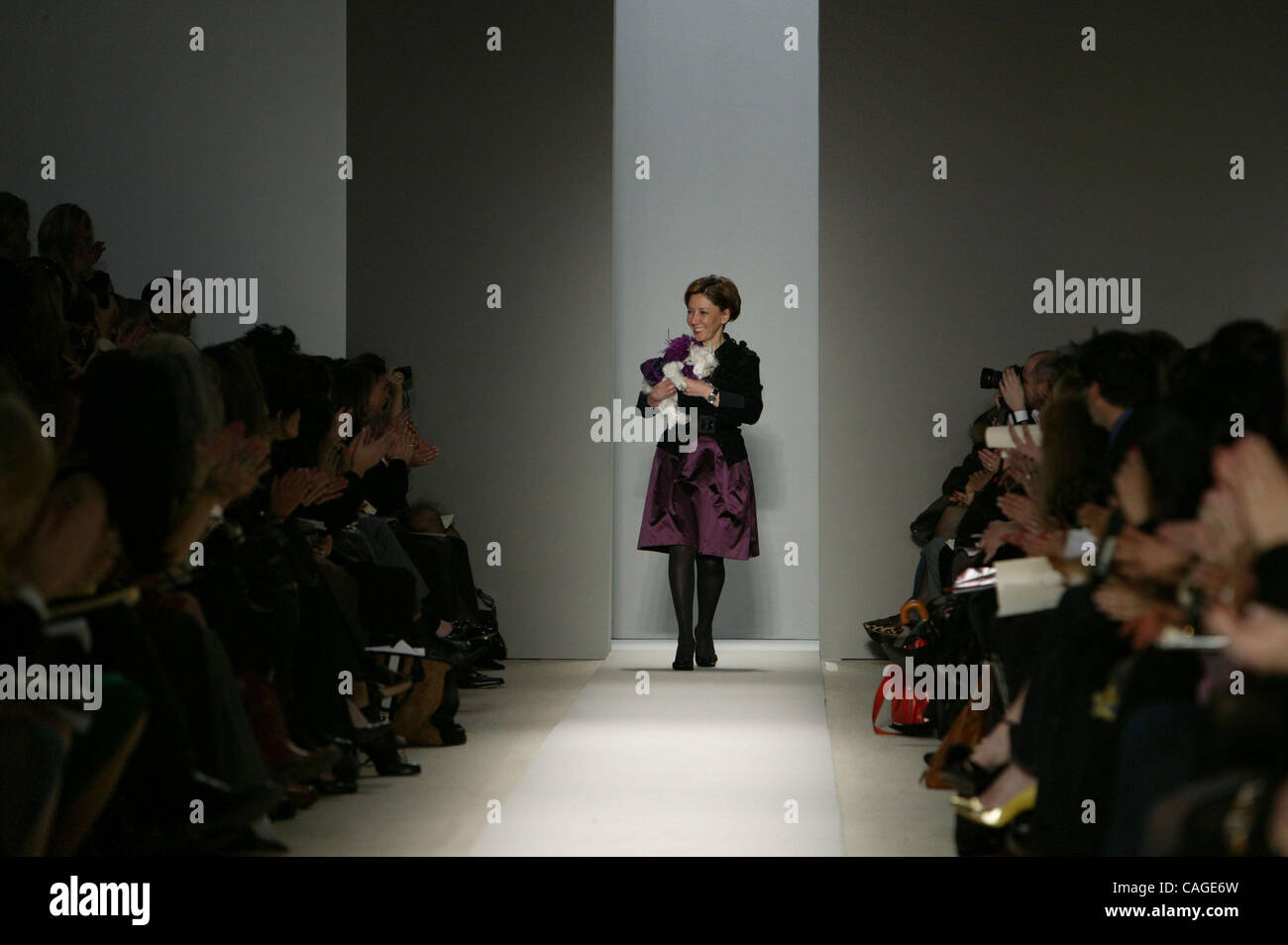 Designer REEM ACRA carries her dog while receiving applause following the REEM ACRA Fall 2008 Fashion Show in New Stock Photo