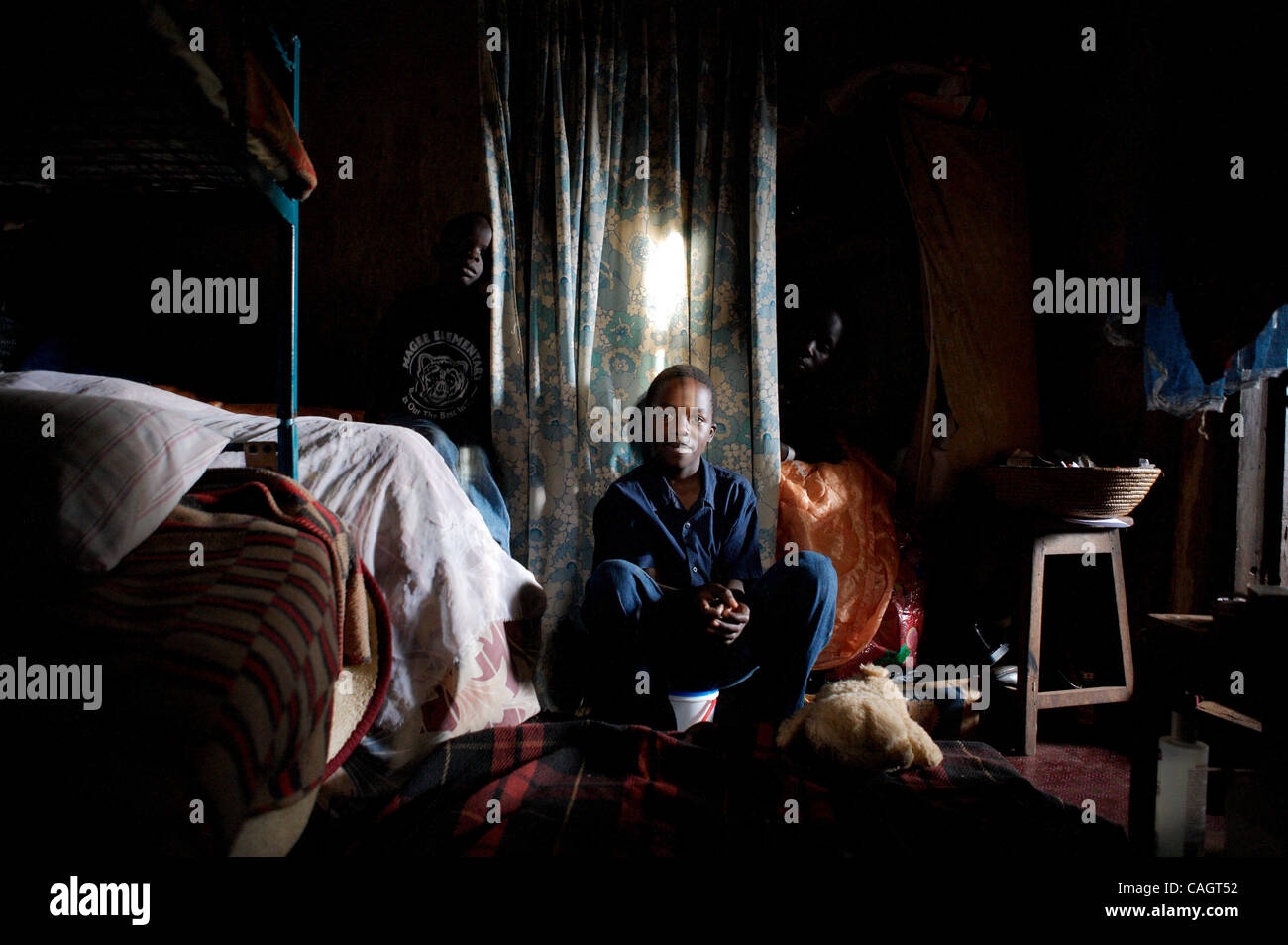This is 13 year-old Gideon Katulume, in the main bedroom of this house, where 3-5 children sleep on each mattress. - Stock Image