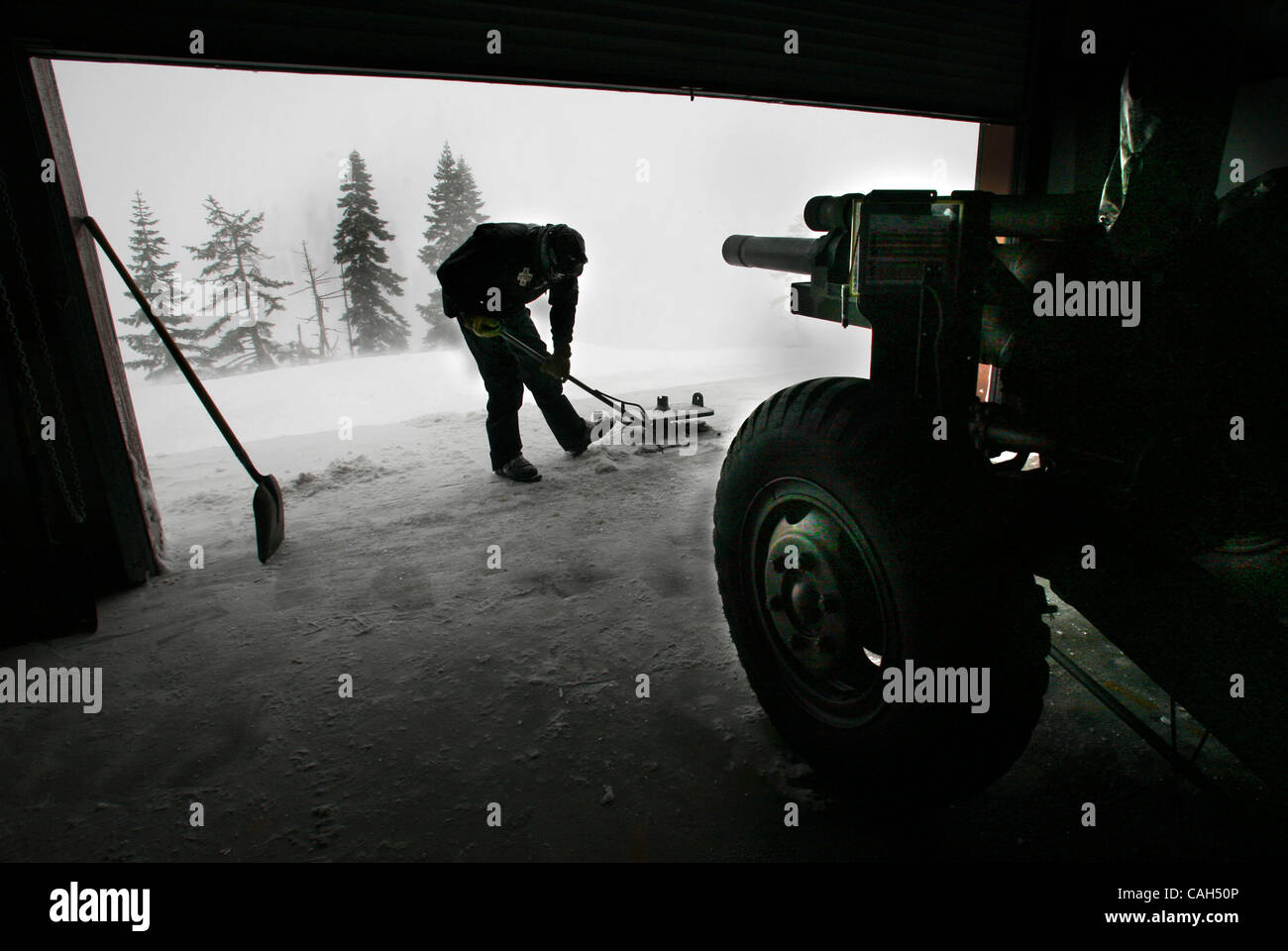 Shane Best an assistant gunner for the World War II Howitzer shovels snow in front of the big gun used to clear Stock Photo