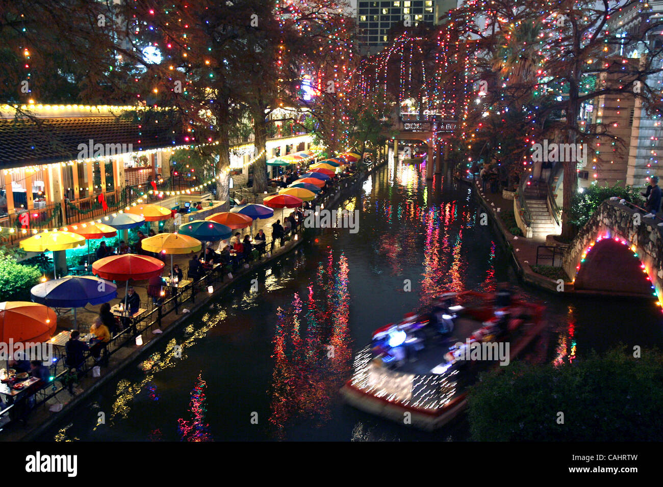metro rivergoers view the christmas lights on the riverwalk while riding in a barge near the