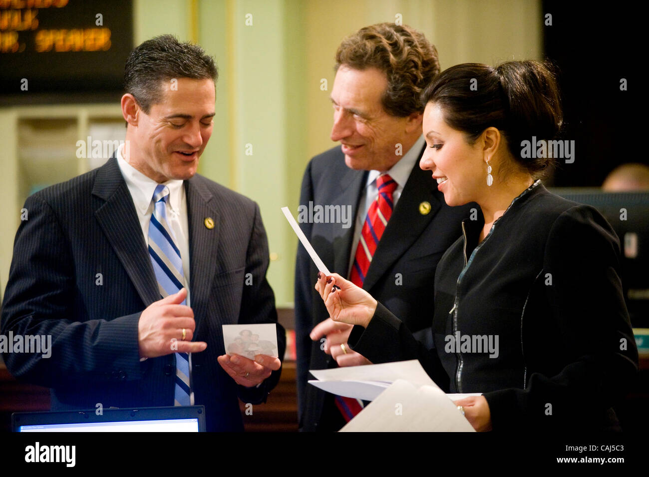 Assembly members L-R, Todd Spitzer, R-Orange, Ira Ruskin, D-Redwood City, and Nicole Parra, D-Hanford, look at Spitzer's - Stock Image
