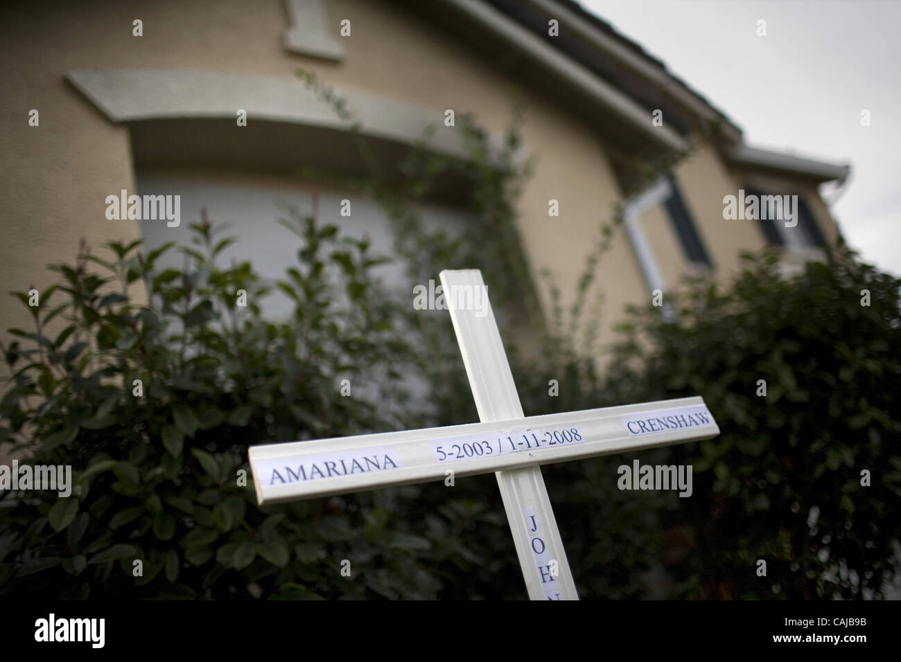 A cross sits outside the house that was involved in an arson fire which claimed the life of 4-year-old Amariana - Stock Image