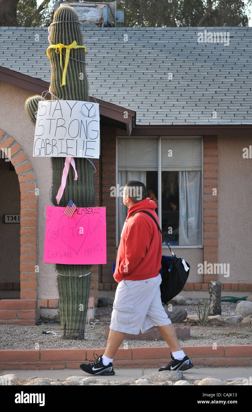 Jan. 10, 2011 - Tucson, Arizona, U.S. -  A Tucson resident walks by a Saguaro cactus that is dressed with posters - Stock Image