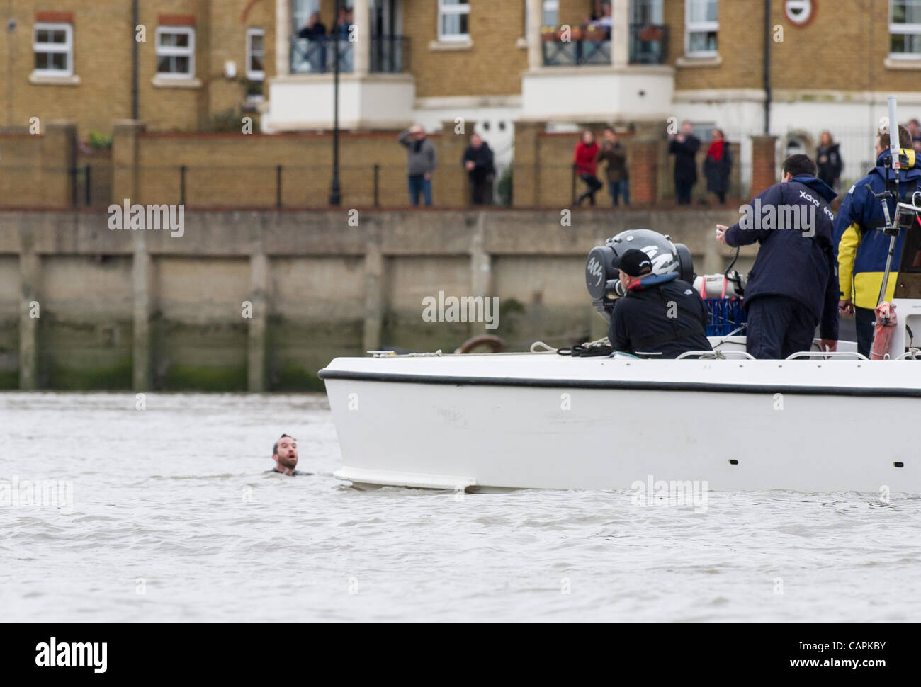 London, UK. 07/04/2012. Man in water halts the 158th Xchanging Oxford & Cambridge Universities Boat Race.   - Stock Image