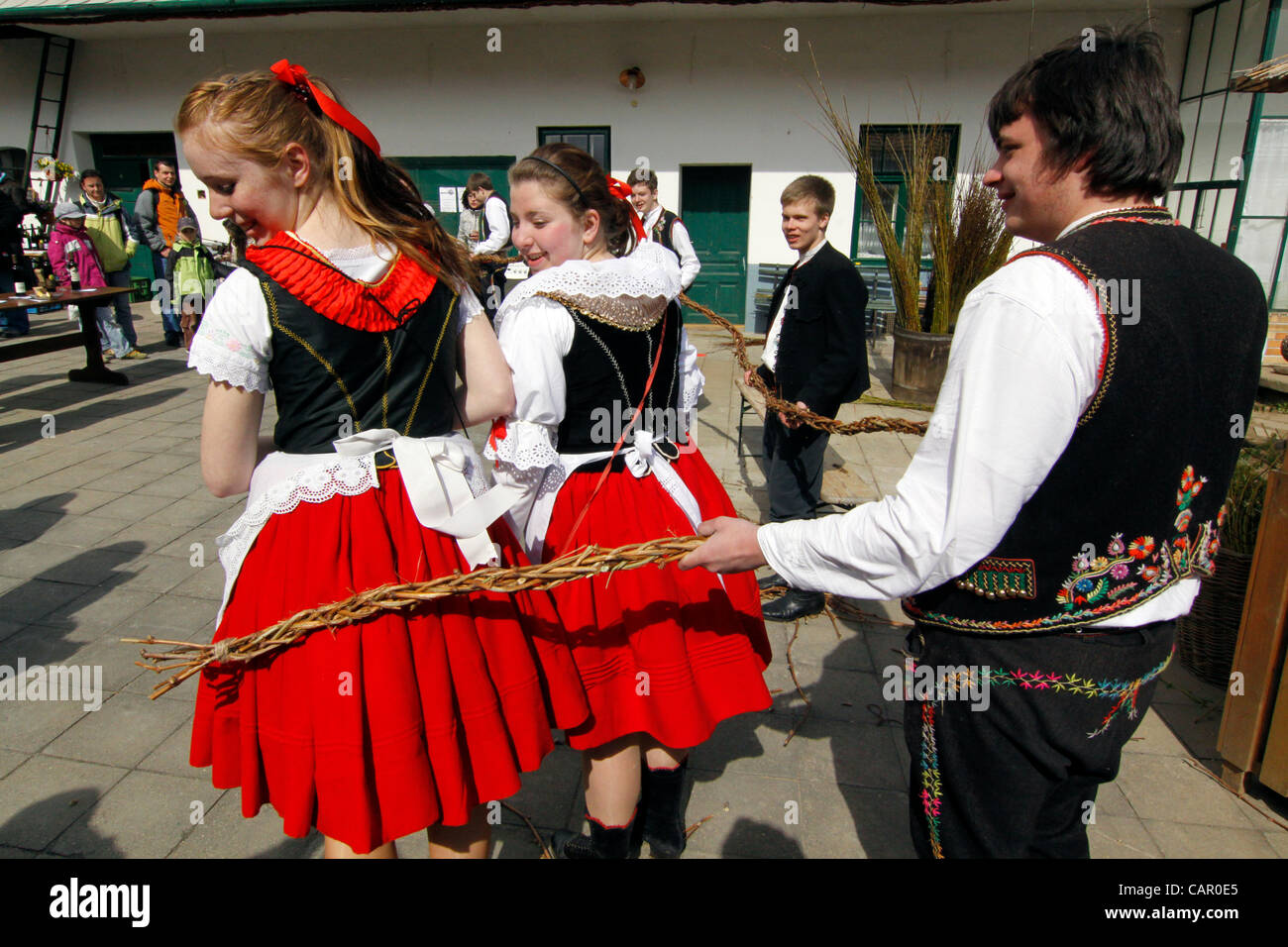 "Boys in folk customs carry a giant ""pomlazka"" (plated willow stems) to whip girls during traditional celebration Stock Photo"