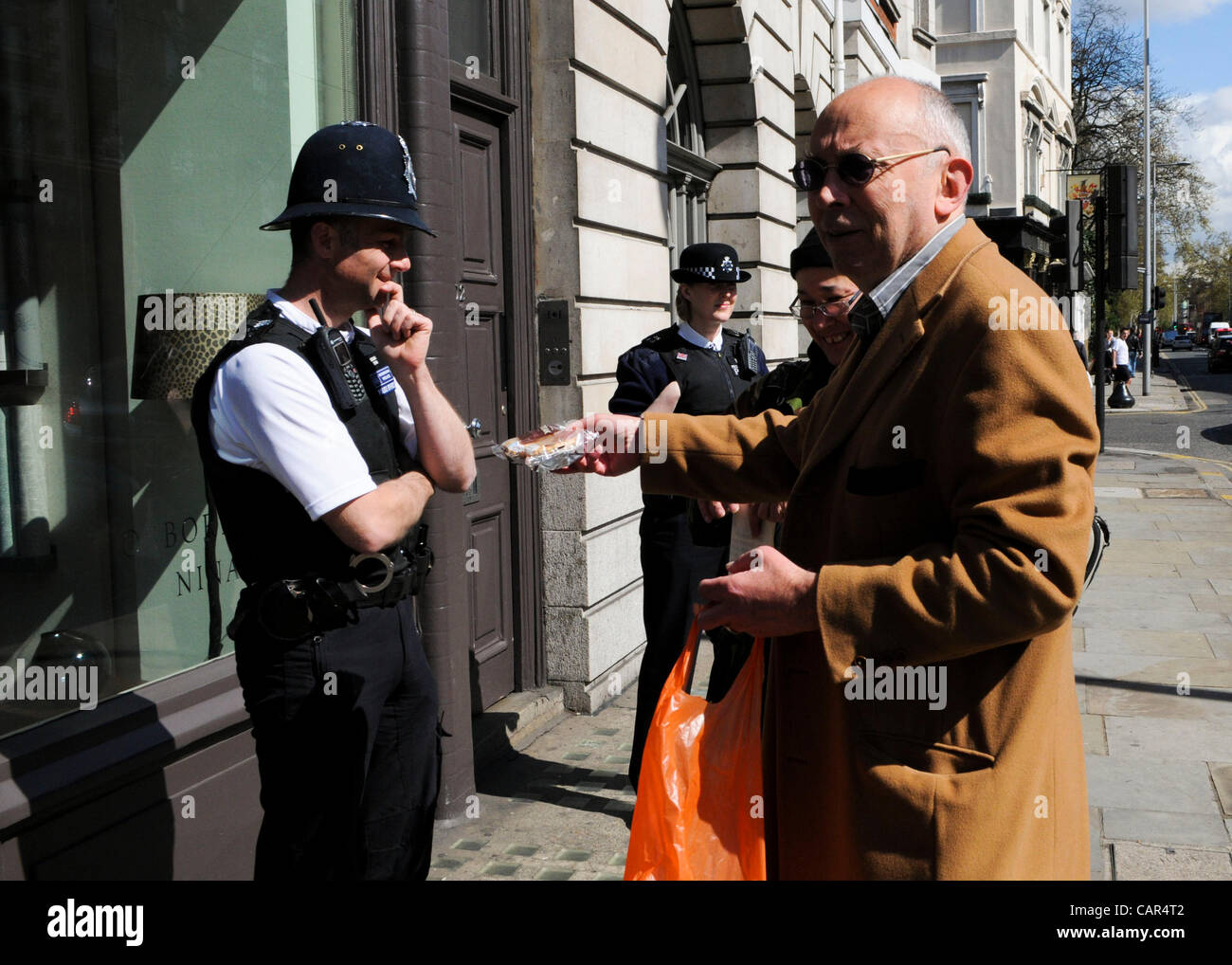 London, UK. 11/04/12. Anarchist, Ian Bone hands a pasty to a policeman. He was delivering pasties to Chancellor - Stock Image