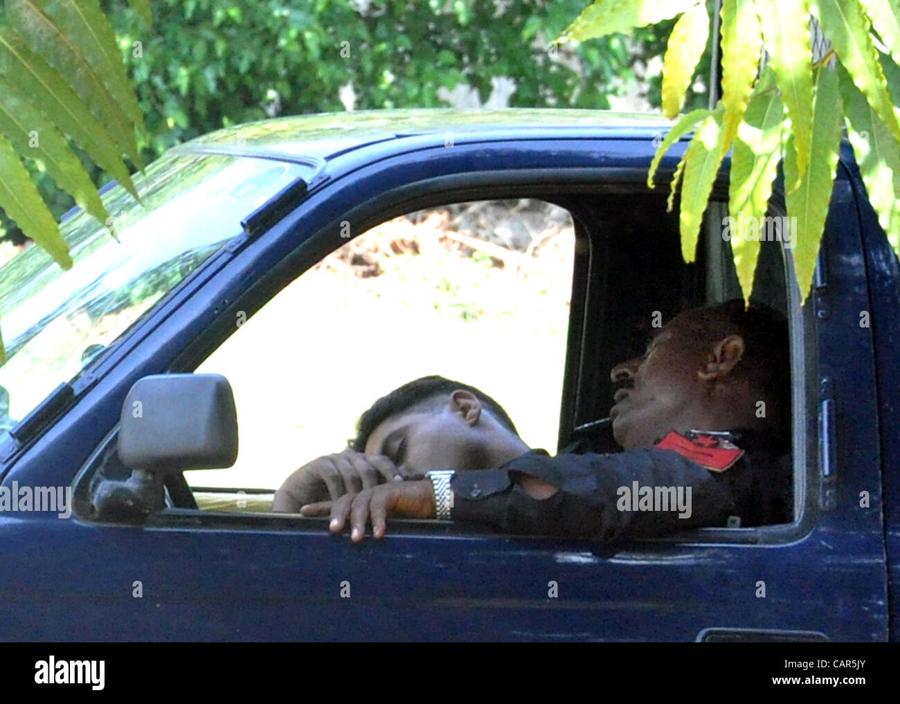 Policemen take nap in police mobile during duty at Royal Palm club in Lahore on Wednesday, April 11, 2012. - Stock Image