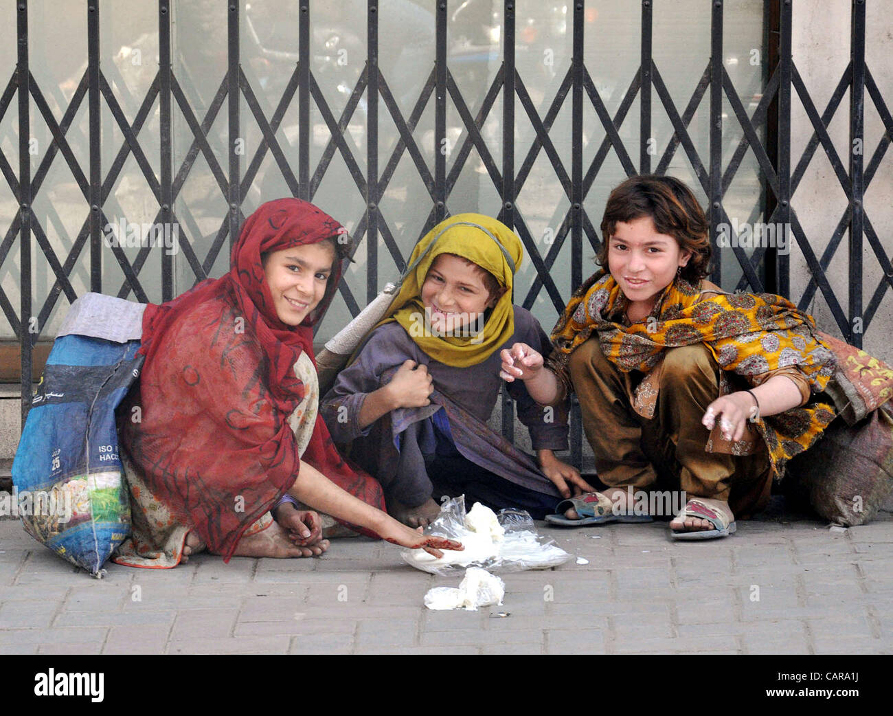 Children, who collect useful items from garbage to earn their livelihood for support their families, sit on a footpath Stock Photo