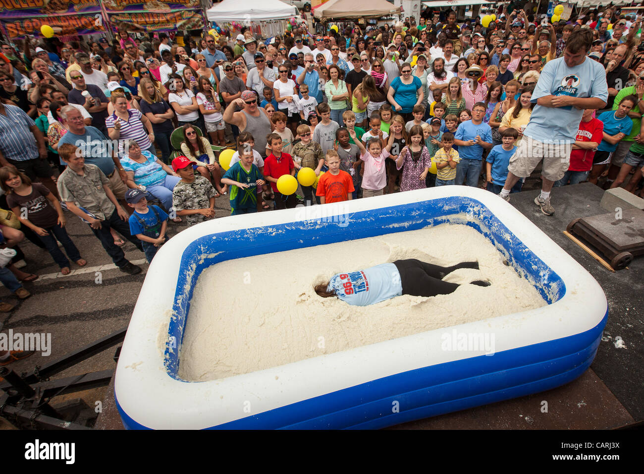A competitor lays face down in a pool of instant grits during the grits roll competition at the World Grits Festival - Stock Image