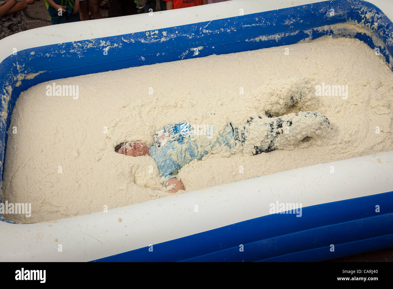 A competitor rolls around in a pool of instant grits during the grits roll competition at the World Grits Festival - Stock Image