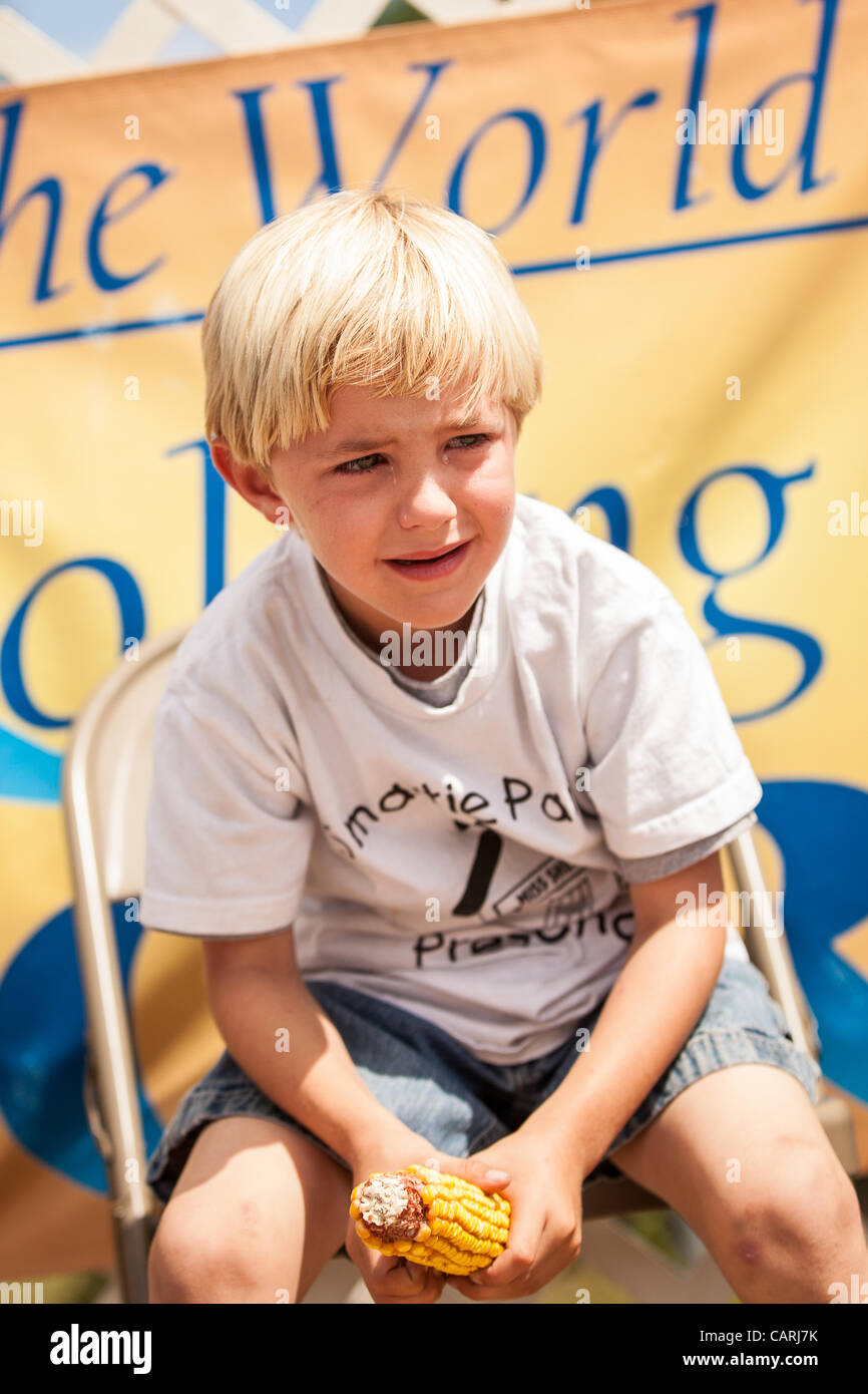 A young competitor tears up as he struggles to husk the most corn at the World Grits Festival April 14, 2012 in - Stock Image