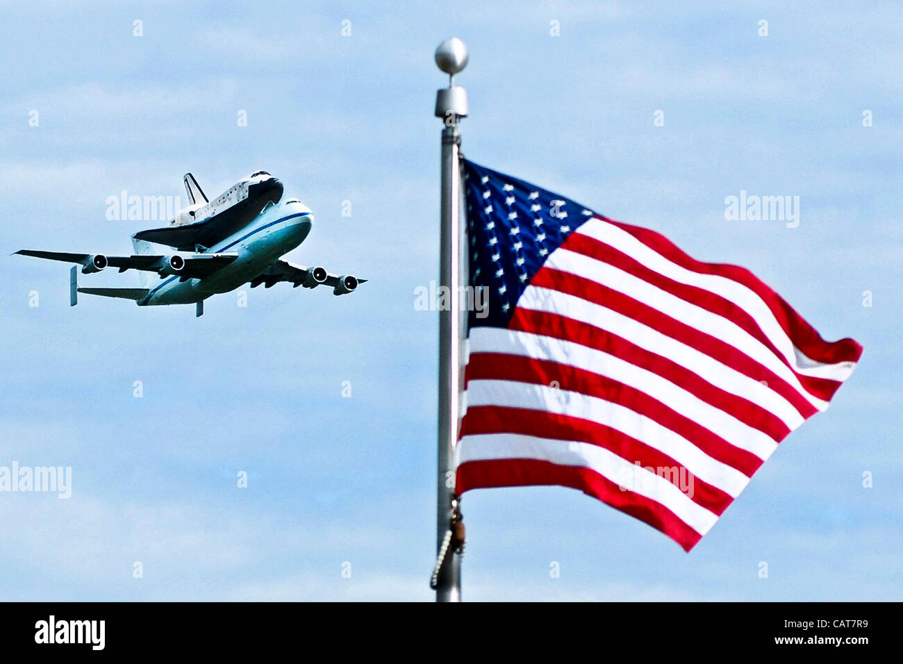 The space shuttle Discovery attached to its 747 transport passes over a US flag during a flyover of the nation's Stock Photo