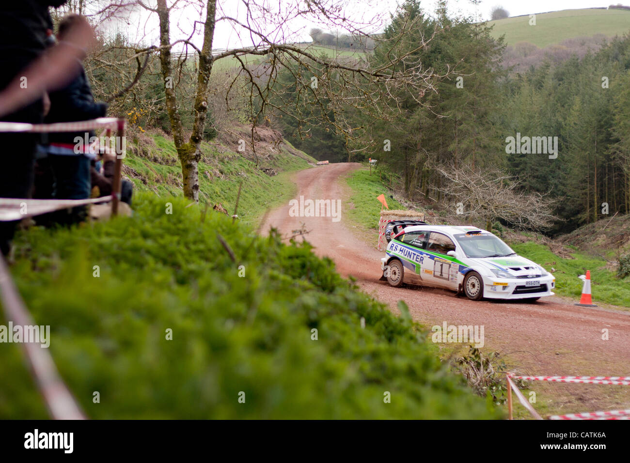 Somerset, UK, 21st April, 2012. Spectators look on as Hugh Hunter competes at the Chargot Woods stage of the 34th - Stock Image