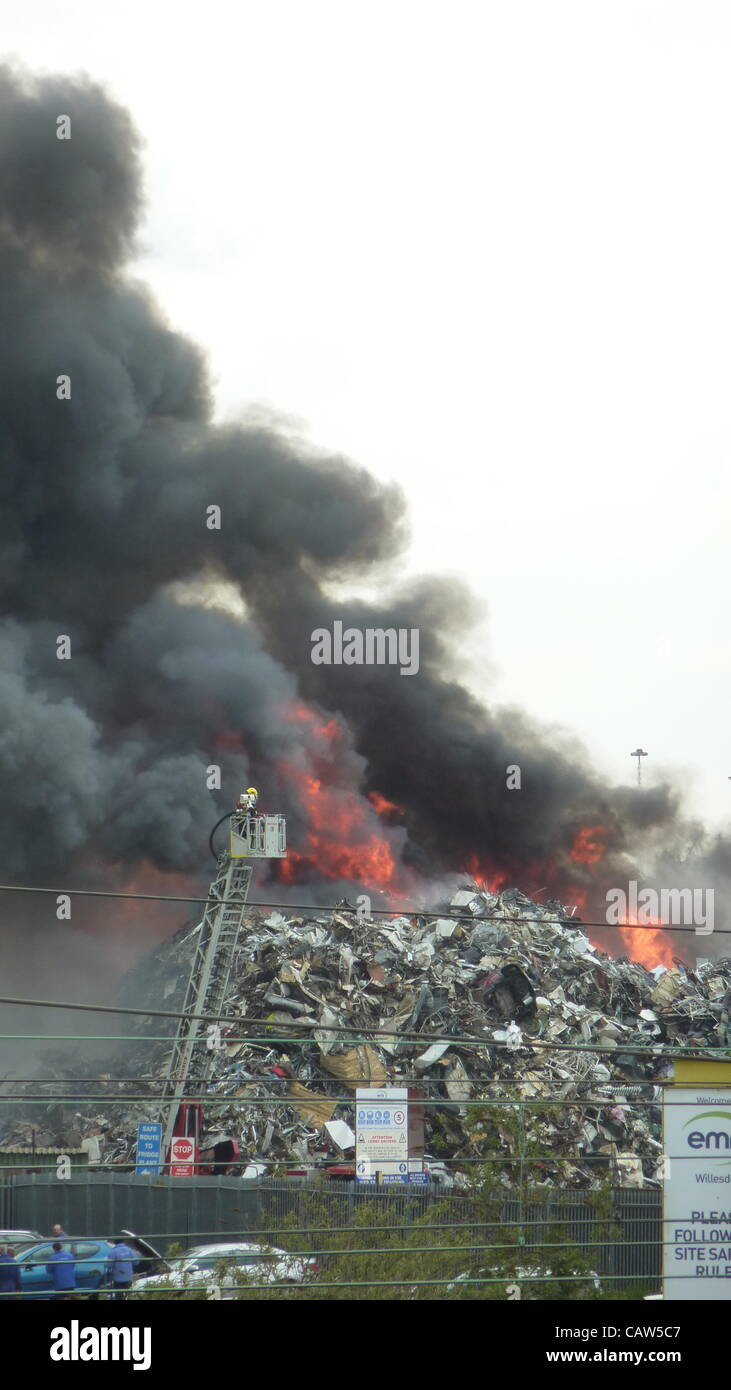 A fire fighter tackles a blaze at a recycling plant in Harlesden  North West London UK on 24 April 2012. - Stock Image