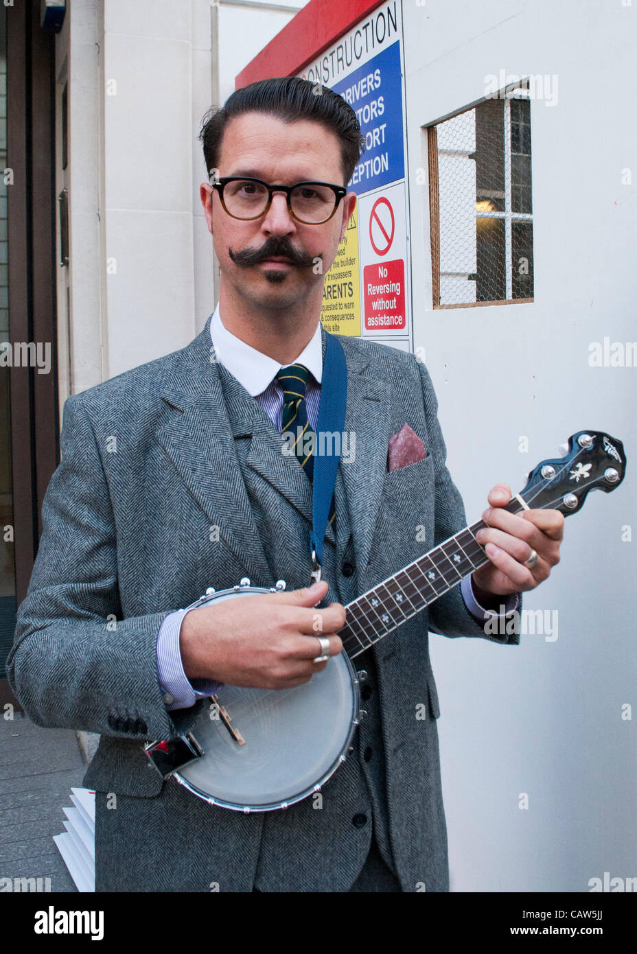 London, UK. 23/04/12. A gentleman plays the banjo as Chaps and Chapette's from the New Sheridan Club holding - Stock Image