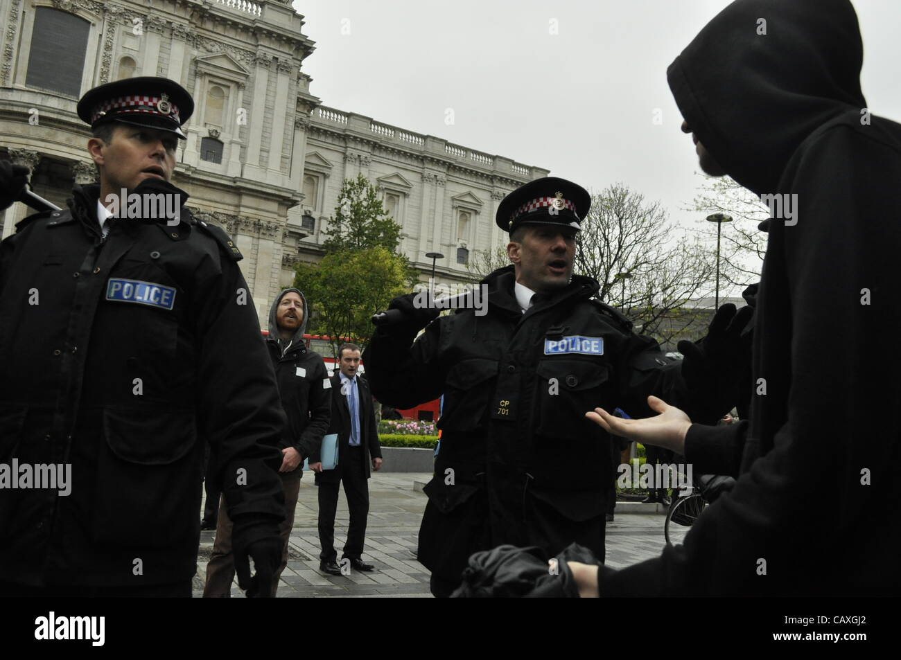 03 May 2012 Carter Lane Gardens, London UK. Policemen wield their batons at a protester during the UK energy summit - Stock Image