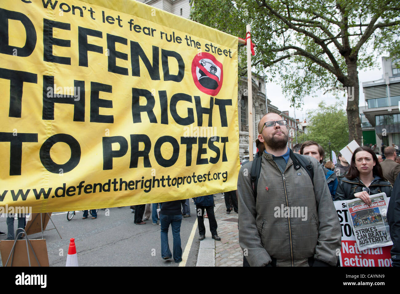 Banner proclaiming the right to protest being held in central London with activists selling Socialist Worker newspaper. - Stock Image