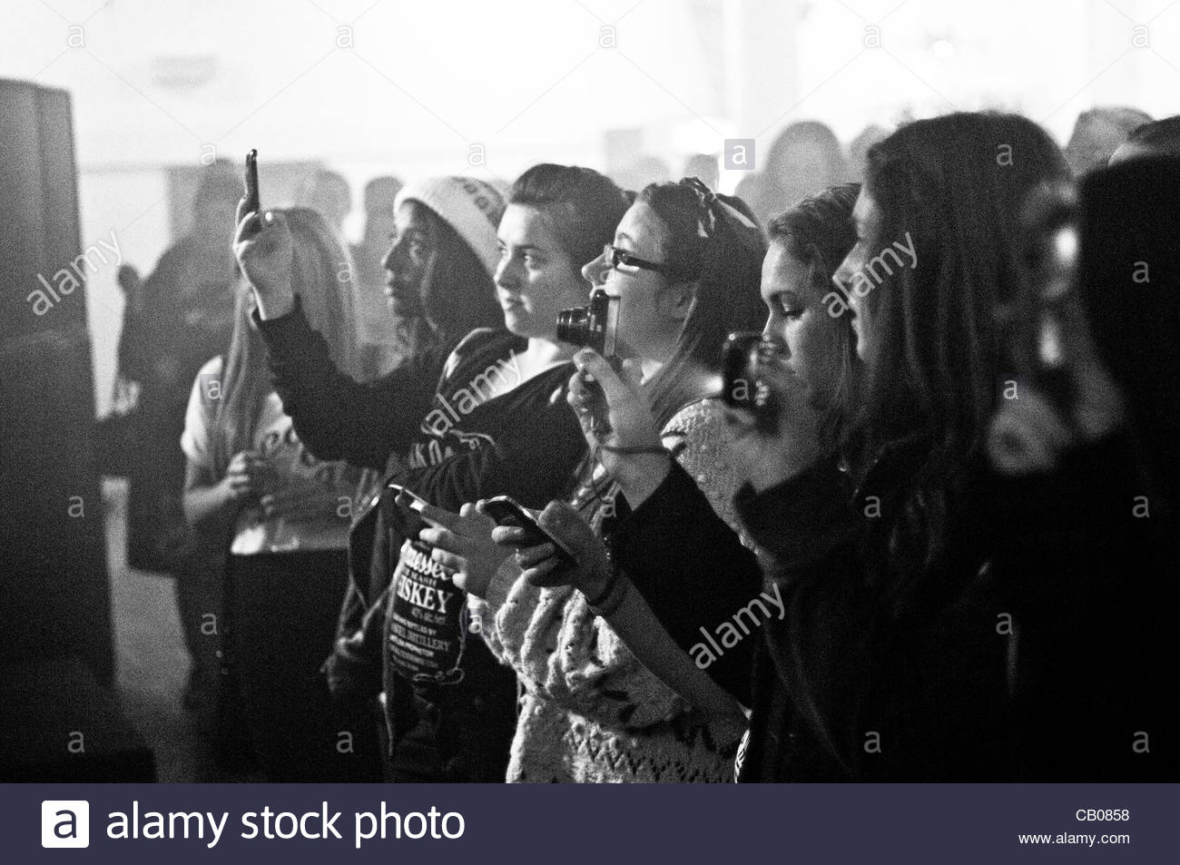 Young female music fans taking photos with cameras and smart phones at the front of a concert for  Alder Hey Charity - Stock Image