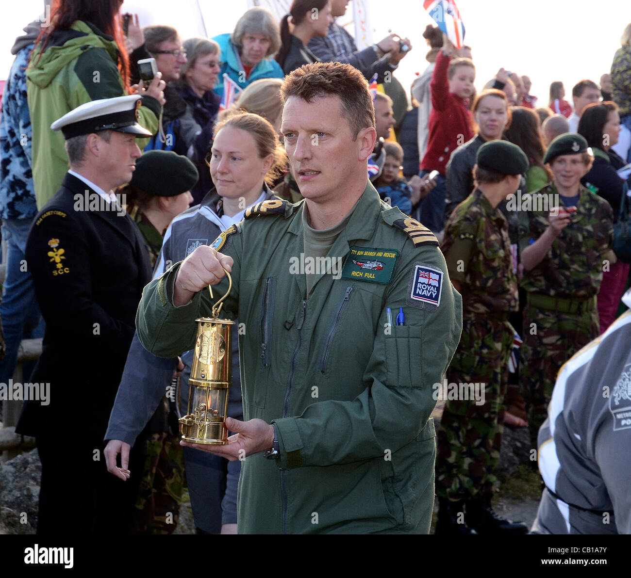 The Olympic Flame arrives at Lands End for the start of the Relay in the safe hands of the Royal Navy Search and - Stock Image