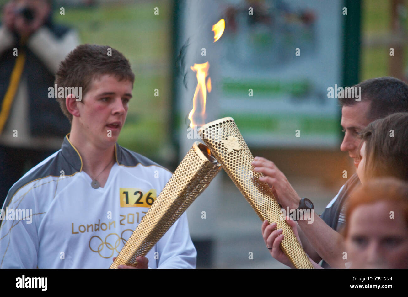 The Olympic Torch relay hands over from one runner to another, with the torch lit from one to another at the handover - Stock Image