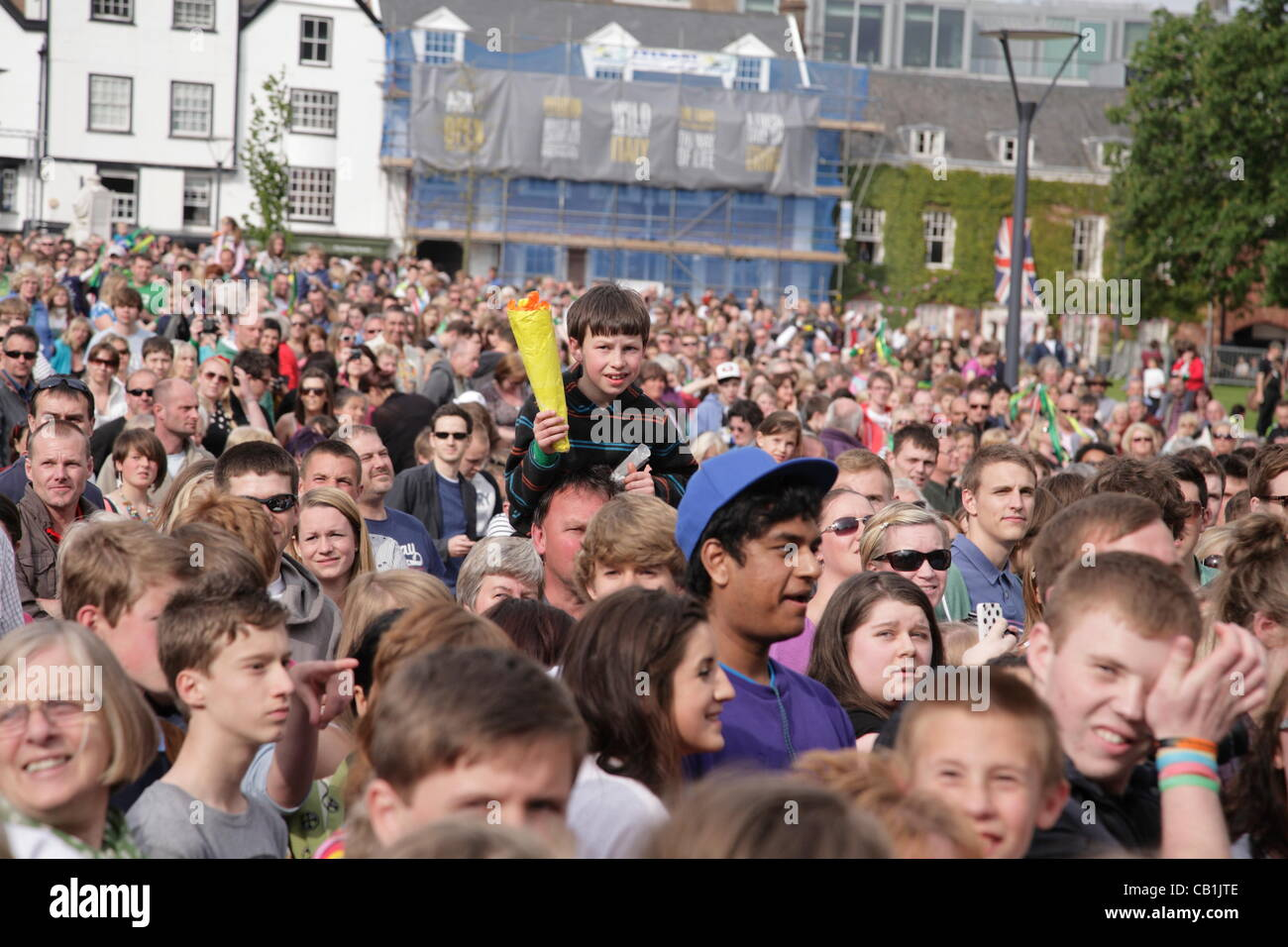 Small boy sitting on a man's shoulders in the crowd holds a home made torch. The Olympic Torch Relay finished - Stock Image
