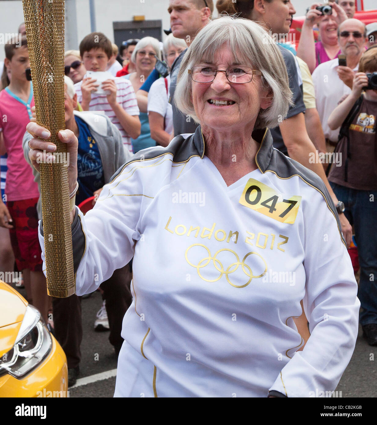 Dorothy Turner aged 70 carrying the flame during the torch relay for the London 2012 Olympics through Abergavenny, - Stock Image
