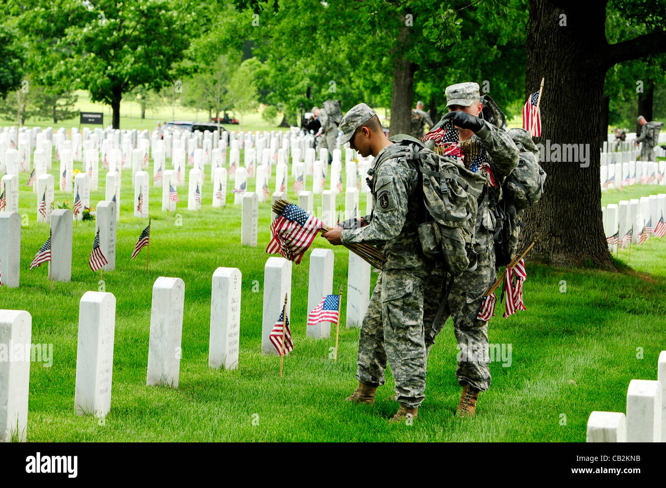 Members of the US 3rd Infantry known as The Old Guard place American flags on grave stones at Arlington National - Stock Image