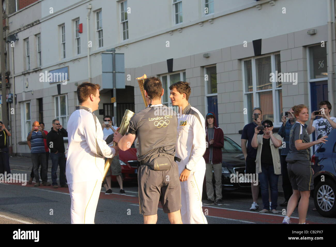 CARDIFF, UK, 26th May 2012. The Olympic flame handover to the next torchbearer. Zak Lee Green (right) passes the - Stock Image