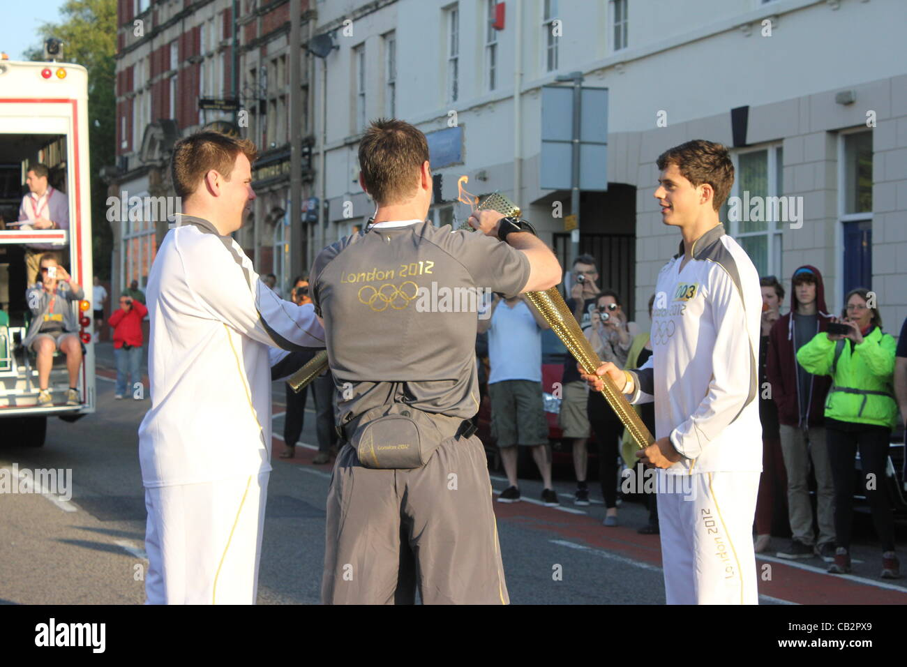 CARDIFF, UK, 26th May 2012. An official supervises as Zak Lee Green (right) hands the Olympic flame over to the - Stock Image