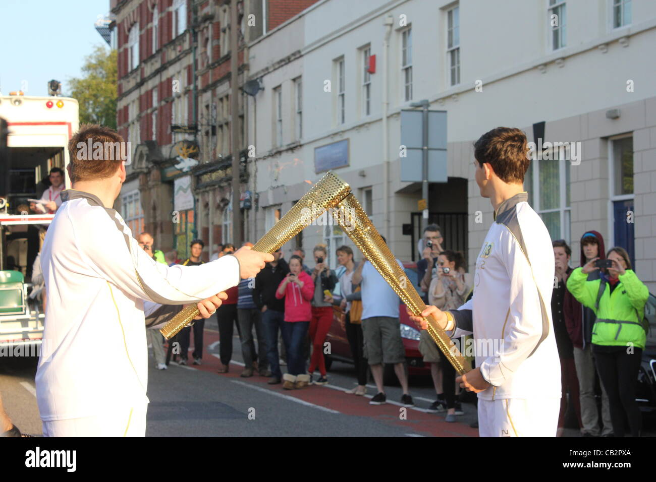 CARDIFF, UK, 26th May 2012. Zak Lee Green, 21, (right) hands the Olympic flame over to the next torchbearer. This - Stock Image